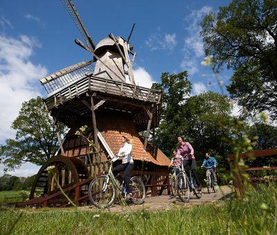 Radfahrer unterwegs auf der Emsland-Route radeln vorbei an der Hüvener Mühle
