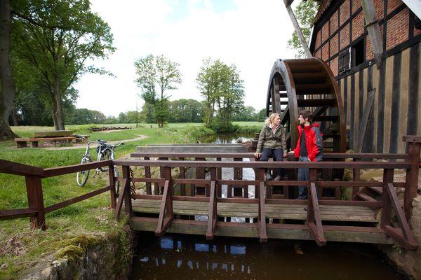 Hüvener Mühle - Radfahrer vor Mühlenrad
